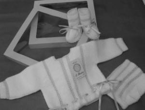Conjunto compuesto por chaqueta, capota y patucos para bebé